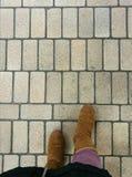 穿棕色靴子、紫色口气裤子和黑外套的女性脚站立在与直线样式的老石路面 免版税库存照片