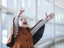 穿橙色外套的嬉戏的小女孩呼喊充满喜悦 免版税库存照片