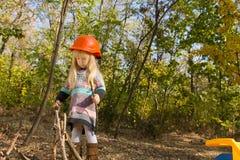 穿橙色安全帽的可爱的小女孩 免版税库存照片