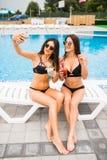 穿比基尼泳装的两名可爱的深色的妇女摆在游泳池附近,做selfie照片 新的成人 免版税图库摄影