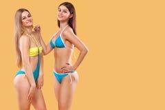 穿泳装和摆在橙色背景的性感的妇女 理想的机体 比基尼泳装夏天与拷贝的广告概念 免版税库存图片