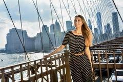 穿流行的服装的美丽的轻松的白肤金发的少妇,摆在布鲁克林大桥 库存图片