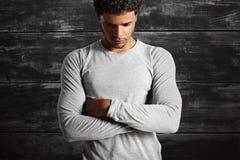 穿浅灰色的longsleeve T恤杉的年轻性感的黑模型 免版税图库摄影