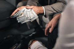 穿深灰夹克的商人给贿款律师 免版税库存照片