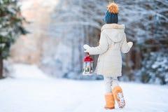 穿温暖的外套的可爱的小女孩户外在拿着手电的圣诞节 库存照片