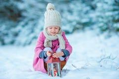 穿温暖的外套的可爱的小女孩户外在拿着手电的圣诞节 免版税库存照片