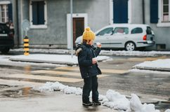 穿温暖的夹克的年轻六岁的男孩室外画象  免版税库存图片