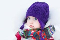 穿温暖的帽子和五颜六色的围巾的逗人喜爱的女婴 免版税库存图片