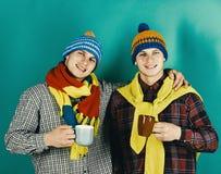穿温暖的帽子和围巾的双胞胎拿着杯子 免版税图库摄影
