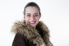 穿温暖的皮大衣的可爱的少妇在冬天 库存照片