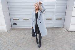穿灰色外套的典雅的年轻blodhair妇女摆在对粗砺的街道墙壁 免版税库存照片
