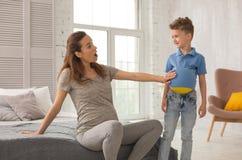 穿灰色衬衣和绑腿的怀孕的母亲欢呼她的儿子 免版税库存图片