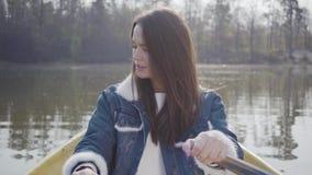 穿牛仔布夹克的一个迷人的女孩的画象漂浮在湖或河的一条小船 美丽的浅黑肤色的男人有效地是 影视素材