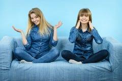 穿牛仔裤服装的两个愉快的妇女朋友 库存图片