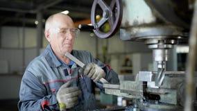 穿特别服装的站立的钻床的年长工厂工人 股票录像