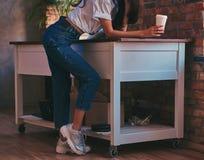 穿白色上面和牛仔裤的一个凉快的现代女孩的播种的图象站立倾斜在与一个杯子的一张桌饭菜外卖点 图库摄影