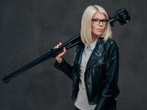 穿白色女衬衫和黑皮夹克的玻璃的秀丽白肤金发的女性摄影师拿着一台专业照相机 库存图片