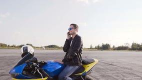 穿皮夹克的一个年轻人坐他的摩托车和获得谈话的乐趣在电话 股票视频