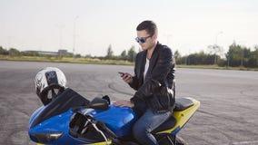 穿皮夹克的一个年轻人坐他的摩托车和获得谈话的乐趣在电话 股票录像