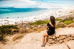穿着一件游泳衣的妇女看从峭壁的海 有的妇女享受夏天和一无忧无虑的holida 库存图片