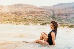穿着一件游泳衣的拉丁白种人妇女,微笑在享用波浪的沙滩 免版税图库摄影