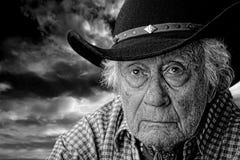 反对风雨如磐的天空的老牛仔 免版税库存照片