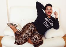 穿着体面俏丽的时髦的非裔美国人的大妈妈的妇女 赃物放松在家,在clothers的豹子印刷品 时尚神色 图库摄影