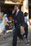 穿着体面的商人发表演讲关于在Passeig de Gri? ¿ ½ cia在扩展区区,拥挤的街的手机在巴塞罗那,西班牙, 免版税库存图片