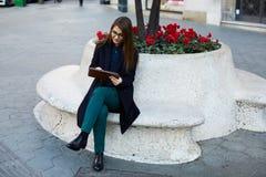 穿着体面的妇女与数字式片剂个人计算机一起使用坐一条石长凳在花床附近 免版税库存图片