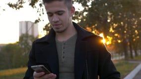 穿着体面的时髦人谈话与手机在日落时间的一个城市 股票视频