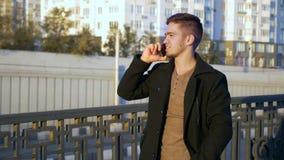 穿着体面的时髦人谈话与手机在日落时间的一个城市 股票录像