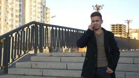 穿着体面的时髦人谈话与手机在日落时间的一个城市 影视素材