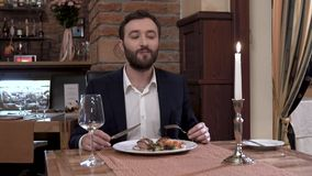 穿着体面餐馆客人的特写镜头,有胡子的确信的年轻人吃着有肉盘的板材在美好的用餐的restaura 股票录像