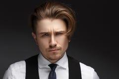 穿着典雅的白色衬衣和黑衣服的英俊的年轻gentelman摆在照相机 库存照片