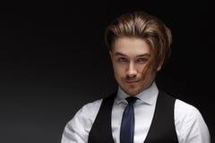 穿着典雅的白色衬衣和黑衣服的英俊的年轻gentelman摆在照相机 库存图片
