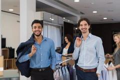 穿着典雅的衣服的两个愉快的微笑的商人站立在现代男服零售店 免版税图库摄影