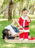 穿着圣诞老人cluas衣服的年轻亚裔母亲对她的儿子 免版税库存照片
