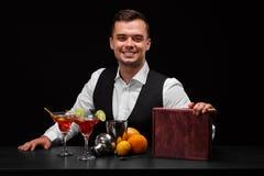 穿着在一个酒吧柜台后的男服务员经典衣服在黑背景 在桌上的很多五颜六色的成份 库存图片
