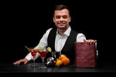 穿着在一个酒吧柜台后的男服务员经典衣服在黑背景 在桌上的很多五颜六色的成份 免版税库存照片