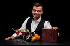 穿着在一个酒吧柜台后的男服务员经典衣服在黑背景 在桌上的很多五颜六色的成份 库存照片