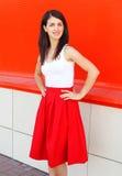 穿着在五颜六色的美丽的微笑的妇女一条红色裙子 免版税库存图片