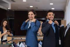 穿着新的衣服的两个英俊的商人,当购物在现代男服零售店时 库存图片