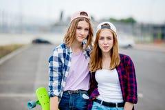 穿着方格的衬衣、盖帽和牛仔布短裤的两个相当微笑的白肤金发的女孩在空的停车场站立与 库存照片