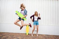 穿着方格的衬衣和牛仔布短裤的两个相当白肤金发的女孩是跳和跳舞与明亮的longboards 年轻 免版税库存照片