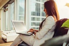 穿着时髦的典雅的白色衣服的母上司侧视图拿着在她的运作在现代办公室的膝部的膝上型计算机 免版税库存图片