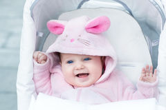 穿着桃红色兔宝宝衣服的可爱的滑稽的女婴 免版税库存照片