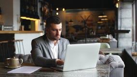穿着灰色衣服,坐在咖啡馆的桌上和使用膝上型计算机的年轻有胡子的商人 股票视频