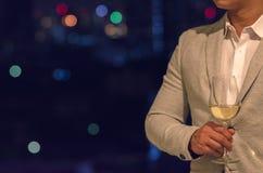 穿着灰色颜色衣服的商人站立在拿着一杯白酒的屋顶酒吧 免版税图库摄影