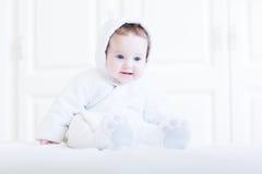 穿着玩具熊雪衣服的滑稽的婴孩 库存照片