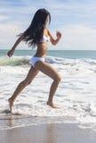 运行在海滩的比基尼泳装的性感的妇女女孩 免版税库存图片